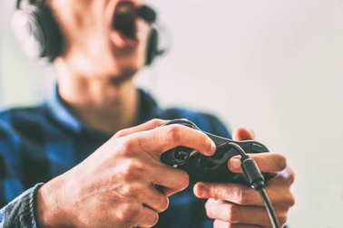 Young man having fun playing video games online using headphones and microphone - Close up male hands gamer holding a joystick - Vintage filter - People, technology, gambling concept