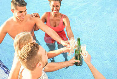 Happy friends cheering with champagne in the pool - Young people having fun making a party and toasting glasses of prosecco - Vacation, holiday, friendship lifestyle concept