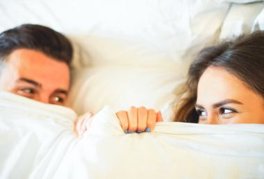 Young playful couple having fun in the bed - Happy lovers looking shy at each other in eyes lying under white sheets in te bedroom at home - Funny and romantic loving concepts - Focus on woman eye