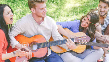Group of friends playing guitars and singing while drinking red wine sitting on grass in a park outdoor - Happy people having fun together making a picnic in the garden - Friendship, lifestyle concept