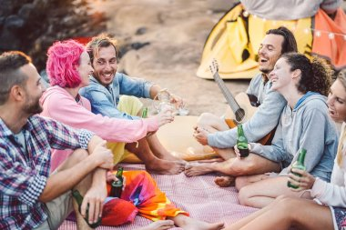 Happy friends having fun camping outdoor - Young people drinking beers and playing guitar in campsite next the beach - Youth culture and travel vacation concept