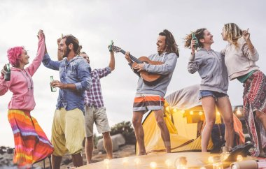 Group friends doing party playing guitar and camping outdoor - Happy young people having fun drinking beer and laughing in camp village - Youth culture lifestyle and vacation travel concept