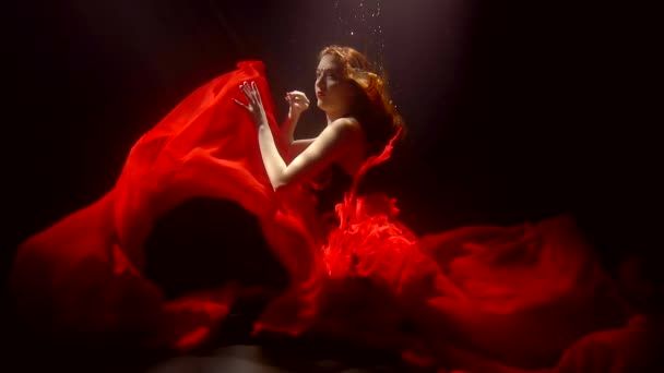 Attractive woman with bright red hair wearing bright red dress doing art underwater in a dark.