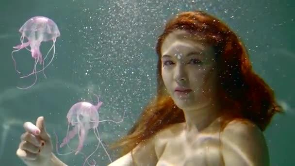 Detailní záběr záběr krásná mořská víla plavání s roztomilý malý jellyfishes