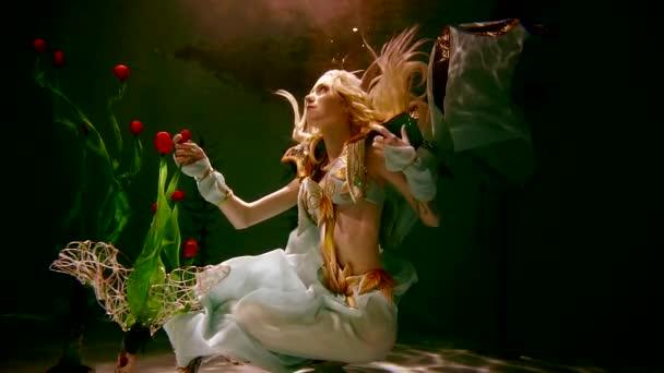fiatal lány a manó jelmez víz alatt tartják a sötétség megvilágítja a fény. szerepjáték.