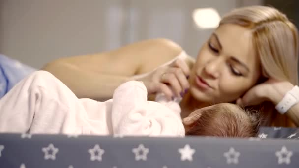 Matka ležela na boku v posteli s malé dítě, které se pohybuje rukou a nohou