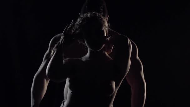 silueta štíhlá žena s Nahá Prsa, stojící v temné a svalnatý velký muž je za ní