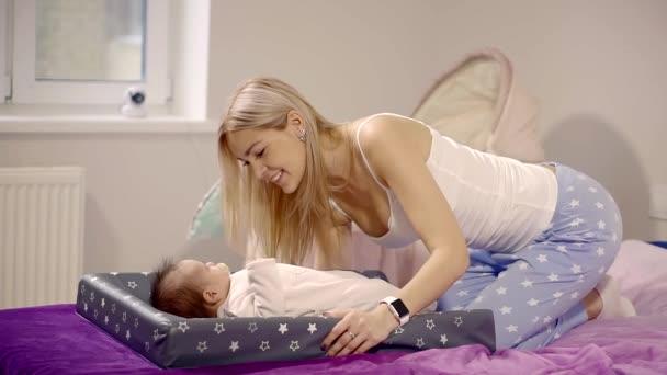 Mladá a krásná dáma je hladila bříško své malé dcery, který se nedávno narodil