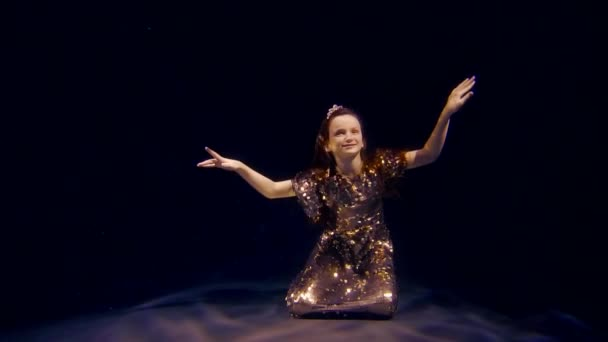 malá princezna mořská víla ve zlatých šatech sedí na dně vodní nádrže, rozhlédl se kolem sebe s rukou