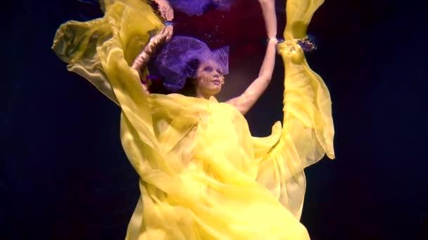 500 képkocka / másodperc. Egy gyönyörű lány, hosszú táncosával lebeg, mint egy angyal víz alatt, mint egy mese