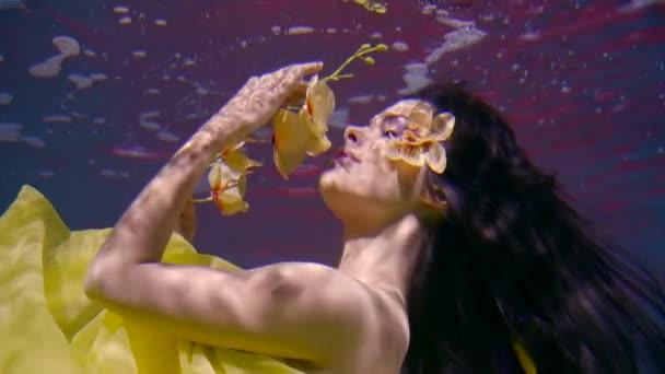 Nádherná žena s dlouhými tmavými vlasy ve žlutých šatech s pobočkou chrysanthemum květiny v jejích rukou plave pod vodou jako v pohádce