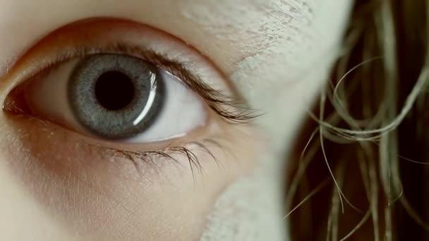 Nahaufnahme der Augen eines Bettlermädchens mit Schlamm im Gesicht.