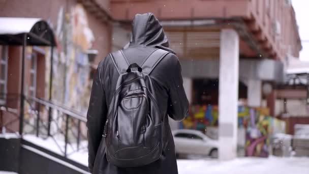 Mysteriöser Mann in schwarzem Mantel spaziert durch verschneite Stadt und raucht