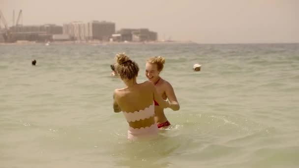 two happy girl friends holding hands splashing in the sea