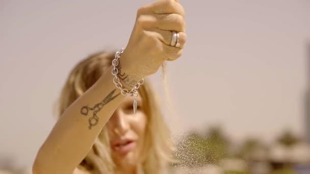 Hermosa Chica Rubia Con Un Tatuaje De Tijeras Y Una Pulsera En La Mano Rocía Todo Alrededor De La Arena