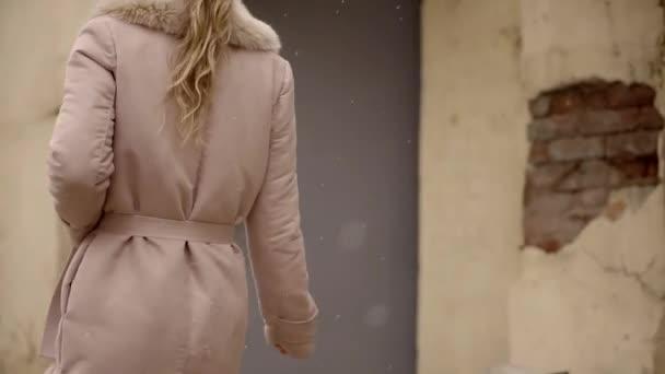 Schlankes blondes Mädchen, das in einem rosafarbenen Mantel aus Naturmaterialien durch die kaputte Straße der Altstadt läuft. der erste Schnee
