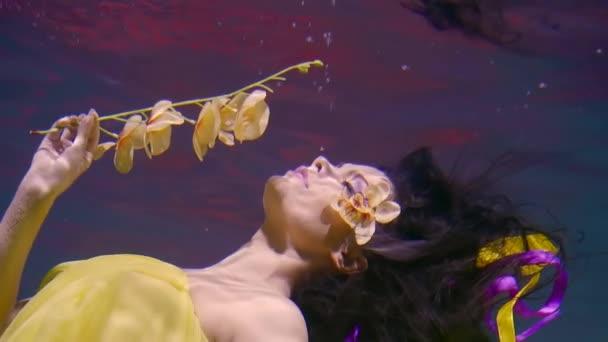 Charmante Meerjungfrau schwimmt unter Wasser mit gelben Blumen, Blütenblätter sind um ihr Auge herum, liegen