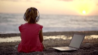 Baby girl watching the sunset with a white wireless headphones on the head. nearby is a working laptop and broadcast the music. a carefree childhood with rich parents