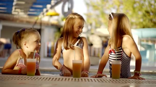 Junggesellenabschied, süße Mädchen tratschen im Pool des Resorts. Kinderpromis im Sommerurlaub mit Cocktails