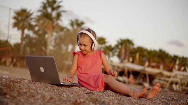 roztomilá dívka v červených šatech sedí na pláži a pracují na přenosném počítači poslech informací o bezdrátových sluchátek s mikrofonem. Vzdálená práce