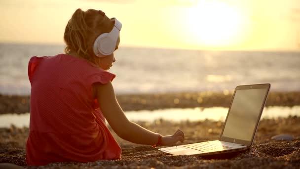 holčičku pracuje s notebookem na pláži při západu slunce. měla na sobě bezdrátové sluchátka k poslechu zvuku. psaní na klávesnici