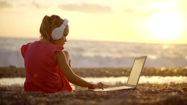 child the freelance on the coast of the sea beyond the laptop to the white headphones on his head