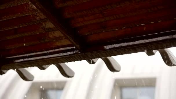 Kapky deště padající z okapu střechy během deště bouře