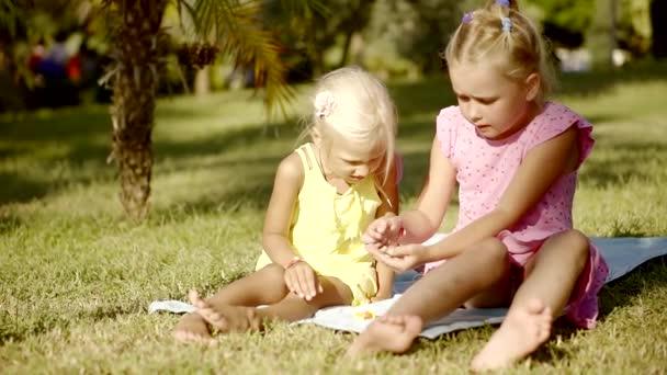 barátnője lányok szőke ül a parkban, a fű és a játék érmék értékük megvitatása