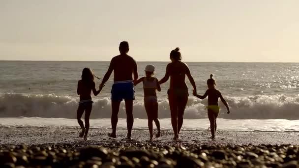 úspěšný mladý početná rodina na moři se svými třemi dcerami. siluety na slunce pozadí