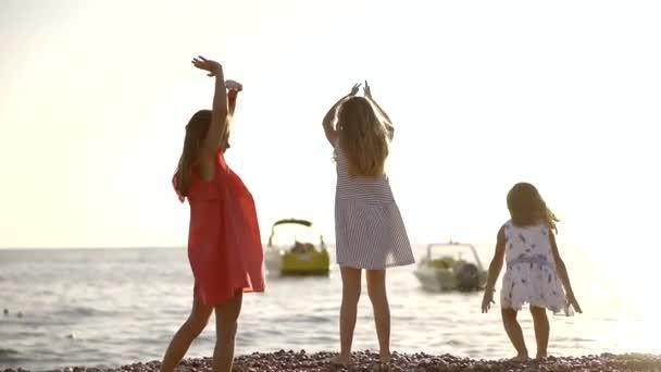 három kislány játszik a tenger partján a nyáron, hogy dobott köveket a víz