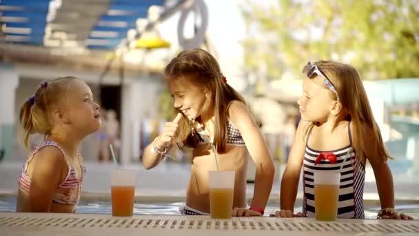 lustiges kleines Mädchen erzählt ihre Freunde komische Geschichte, lacht zusammen, steht im Schwimmbad