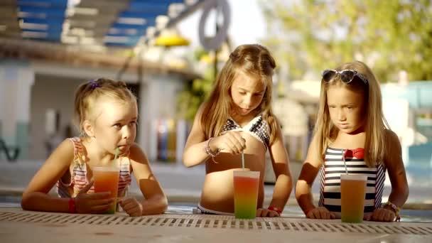 drei süße kleine Mädchen ist in einem Swimmingpool, Mixen und trinken saftigen Cocktail in den Sommerferien