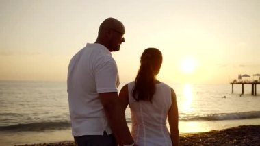 high bald man with his graceful dark-haired wife are standing on an ocean coast and enjoying sunset