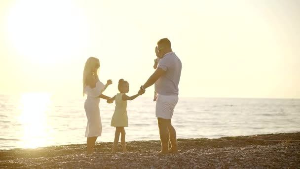 happy parents are embracing their little loved daughters in pebble beach in evening time