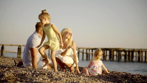 family is having fun on a beach in evening time, they are throwing stones to a sea water