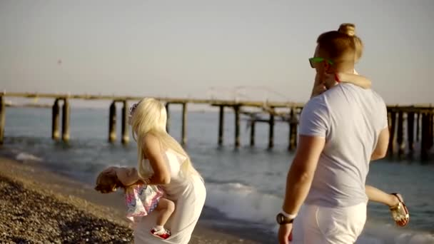 happy adult man and woman are holding their daughters on hands and playing on a sea shore