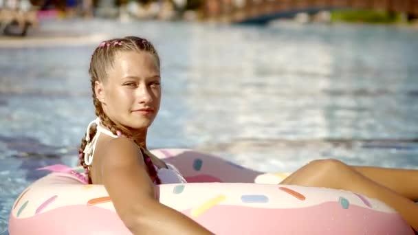 radostné dospívající dívka sedí v růžové nafukovací kruh, plovoucí na bazén v aquaparku v letním dni