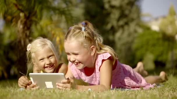 due piccole ragazze bionde sono sorridente e ridere, sdraiato sullerba in un cantiere in giornata e utilizzando una tavoletta