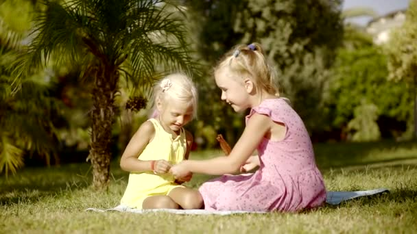 two cheerful little sisters are sitting on a grass and playing in a garden in summer vacation