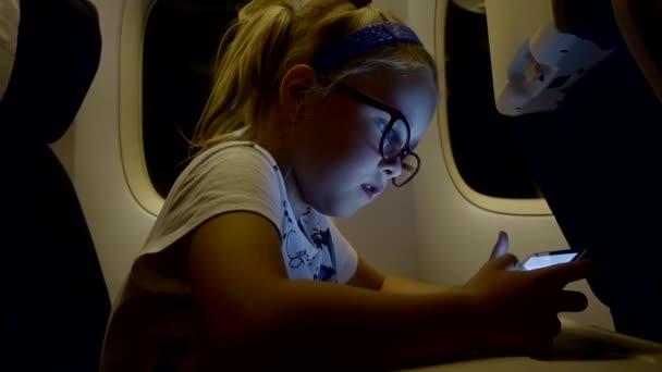 kleine blonde Mädchen sitzt in einem Flugzeug in der Nähe ein Bullauge und Computerspielen auf dem tablet