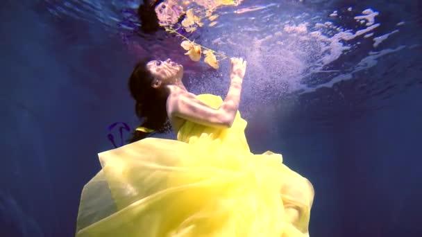 mladá žena s květinou v ruce je ponořen v moři, z vrcholu je její reflexe na vodách hrany