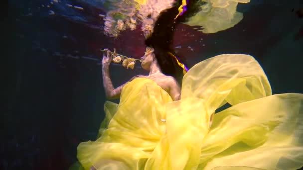 elegantní ženy v nádherné šaty v ruce mával její oblečení pod vodou, je květina