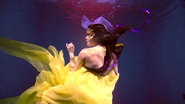 mladá žena v nádherné šaty tance pod vodou v svěží a jasné šaty