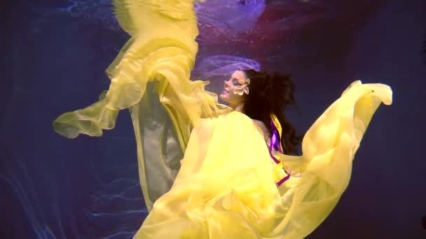 mladá žena v nádherné šaty je pod vodou, žlutý květ je vložena na oku
