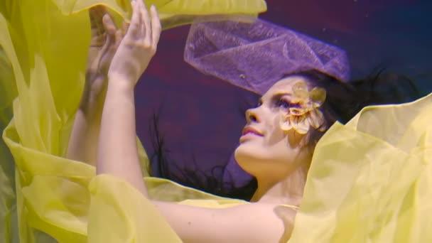 mladá herečka tančí tanec pod vodou, je oblečen v zářivě žluté šaty a na její tváři je květina