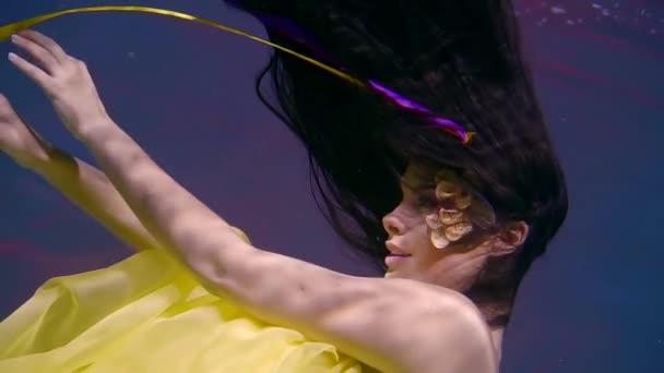 krásná žena jako mořská panna má plavání pod vodou v bazénu, je oblečen ve žlutých šatech