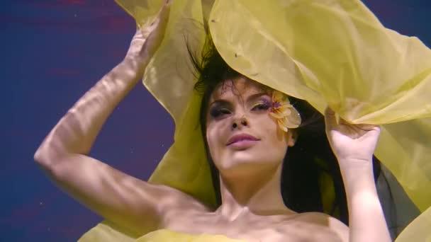 portrét mladé ženy, která hravě tančí pod vodou, dáma drží lem šaty