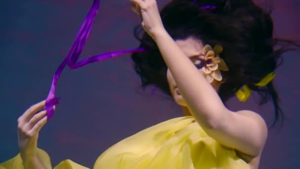 Mladá herečka tance pod vodou, lady ukazuje výkon v zářivě žluté šaty