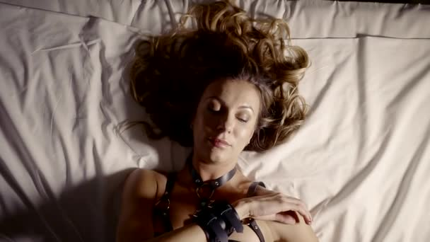 Atraktivní sexy žena ležela v posteli v poutech