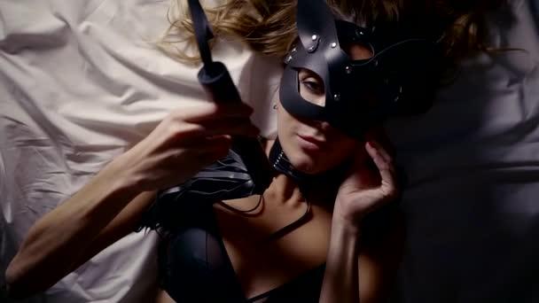 Schuss aus einer sexy Frau mit Leder Unterwäsche und schwarze Maske.